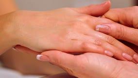 Cuidado de la mano en el salón de belleza Dé masajes a los fingeres y a la muñeca en un salón del balneario Procedimiento de la m metrajes