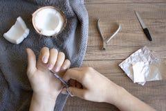 Cuidado de la mano, cuidado popular de la mano Manicura con el aceite de coco, herramientas de la manicura: tijeras, fichero de c foto de archivo