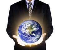 Cuidado de la tierra con las manos de ayuda del hombre de negocios Imágenes de archivo libres de regalías