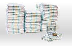 Cuidado de niños costoso Una pila de pañales y de dinero en el fondo blanco fotos de archivo