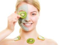 Cuidado de pele Mulher na máscara da argila na cara e no quivi Foto de Stock Royalty Free