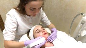 Cuidado de pele A mulher no salão de beleza da cosmetologia obtém a massagem do lpg em sua cara filme