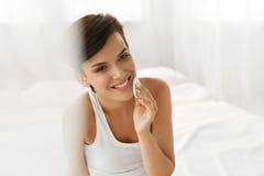 Cuidado de piel de la belleza Mujer que quita maquillaje de la cara usando el cojín de algodón Imagen de archivo