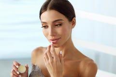 Cuidado de piel de los labios Mujer con la cara de la belleza que aplica protector labial encendido imagen de archivo libre de regalías