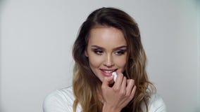 Cuidado de piel del labio Mujer con el maquillaje de la belleza que aplica bálsamo en los labios metrajes