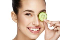 Cuidado de piel del ojo Mujer con maquillaje natural usando el pepino foto de archivo libre de regalías