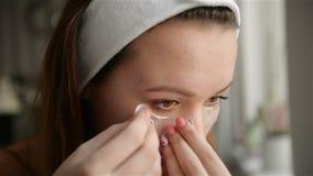 Cuidado de piel de la belleza Muchacha hermosa que aplica el remiendo blanco de la nariz en piel facial Modelo femenino joven Wit metrajes
