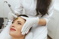 Cuidado de piel de la cara Mujer que consigue el tratamiento Exfoliating hidráulico facial fotos de archivo libres de regalías