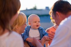 Cuidado de quatro adultos sobre o bebê fotografia de stock royalty free