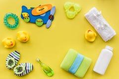 Cuidado del bebé con el sistema, los anadones y la toalla del baño en maqueta amarilla de la opinión superior del fondo Foto de archivo libre de regalías