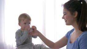 Cuidado del bebé, muchacho gritador del niño que bebe el agua mineral pura del vidrio de los brazos jovenes de la mamá al amortig almacen de metraje de vídeo