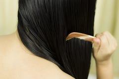 Cuidado del cabello Primer del pelo hermoso de Hairbrushing de la mujer con el cepillo Retrato de la mujer femenina atractiva que imagen de archivo libre de regalías