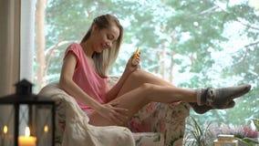 1d792387d76 Cuidado del cuerpo de la mujer joven en sala de estar acogedora almacen de  metraje de