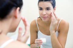 Cuidado del cuerpo. Mujer que aplica la crema en cara Fotografía de archivo libre de regalías