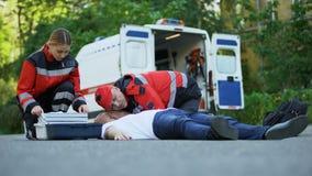 Cuidado del personal de servicio de ambulancia para el paciente en el camino, poniendo el equipo intravenoso almacen de metraje de vídeo