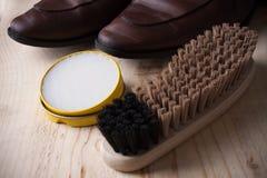Cuidado del zapato Cera y cepillos del zapato en superficie de madera Zapatos de Glacage Imagenes de archivo