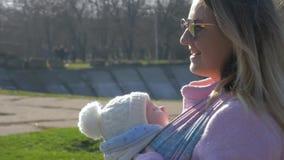 Cuidado do bebê, fêmea de sorriso nos óculos de sol com passeio recém-nascido ao longo da rua filme