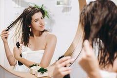 Cuidado do cabelo e do corpo Mulher feliz nova na toalha branca que aplica a máscara no cabelo no banheiro, reflexão do condicion fotografia de stock