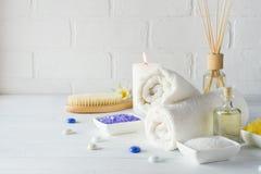 Cuidado do corpo ajustado descascando Com toalha, o lírio branco, sal do mar, óleo de banho, corpo do açúcar esfrega, faz massage foto de stock
