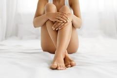 Cuidado do corpo da mulher Feche acima dos pés longos com pele e mãos macias Imagens de Stock Royalty Free