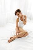Cuidado do corpo da mulher Menina bonita que toca na pele macia dos pés longos imagens de stock