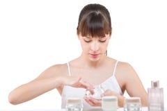 Cuidado do corpo: Mulher nova que aplica a loção no banheiro Imagem de Stock
