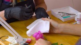 Cuidado do prego do dedo do close up pelo especialista do tratamento de mãos no salão de beleza O manicuro pinta pregos com verni video estoque