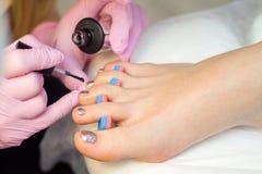 Cuidado do prego e conceito do pedicure As mãos do manicuro do close up em luvas cor-de-rosa estão pintando o verniz para as unha fotos de stock royalty free