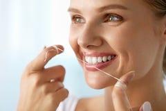 Cuidado dos dentes Mulher de sorriso bonita que Flossing os dentes brancos saudáveis imagens de stock