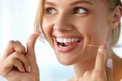 Cuidado dos dentes Mulher de sorriso bonita que Flossing os dentes brancos saudáveis imagens de stock royalty free