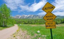 Cuidado: A estrada áspera assina dentro as montanhas de San Juan em Colorado Fotos de Stock