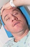 Cuidado médico: Hombre en cama de hospital Foto de archivo libre de regalías