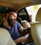Cuidado masculino do barbeiro Trabalho remoto Tempo do café fast food - cachorro quente Moderno caucasiano brutal com bigode Home fotos de stock royalty free