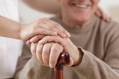 Cuidador útil y viejo hombre feliz foto de archivo