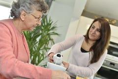 Cuidador casero que sirve un té a una señora mayor fotos de archivo
