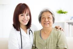 Cuidador casero sonriente con la mujer mayor fotografía de archivo
