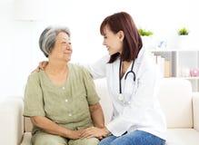 Cuidador casero sonriente con la mujer mayor imagen de archivo