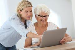 Cuidador casero y mujer mayor que usa el ordenador portátil fotografía de archivo libre de regalías