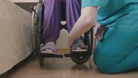 Cuidador femenino que ayuda a la mujer mayor a poner sus zapatos metrajes
