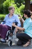 Cuidador femenino que habla con la mujer perjudicada en la silla de ruedas Foto de archivo libre de regalías