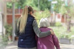 Cuidador joven que camina con la mujer mayor en el jardín con el fondo ligero imagenes de archivo