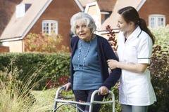 Cuidador que ayuda al hombre mayor a caminar en jardín usando marco que camina Imagen de archivo libre de regalías