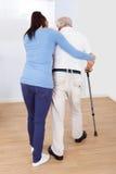 Cuidador que ayuda al hombre mayor para caminar con el palillo Fotos de archivo libres de regalías