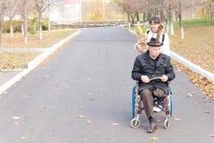 Cuidador que ayuda a un hombre discapacitado en una silla de ruedas Imagenes de archivo