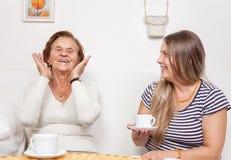Cuidador que come una taza de té con una mujer mayor fotos de archivo libres de regalías