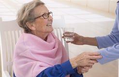Cuidador que da el vidrio de agua a una mujer mayor elegante foto de archivo libre de regalías