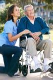 Cuidador que empuja al hombre mayor en silla de ruedas Imagen de archivo libre de regalías