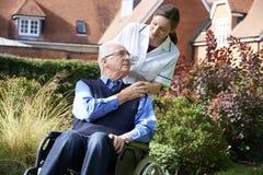 Cuidador que empuja al hombre mayor en silla de ruedas imagen de archivo