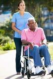 Cuidador que empuja al hombre mayor infeliz en silla de ruedas Foto de archivo libre de regalías