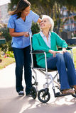 Cuidador que empuja a la mujer mayor en silla de ruedas Imágenes de archivo libres de regalías